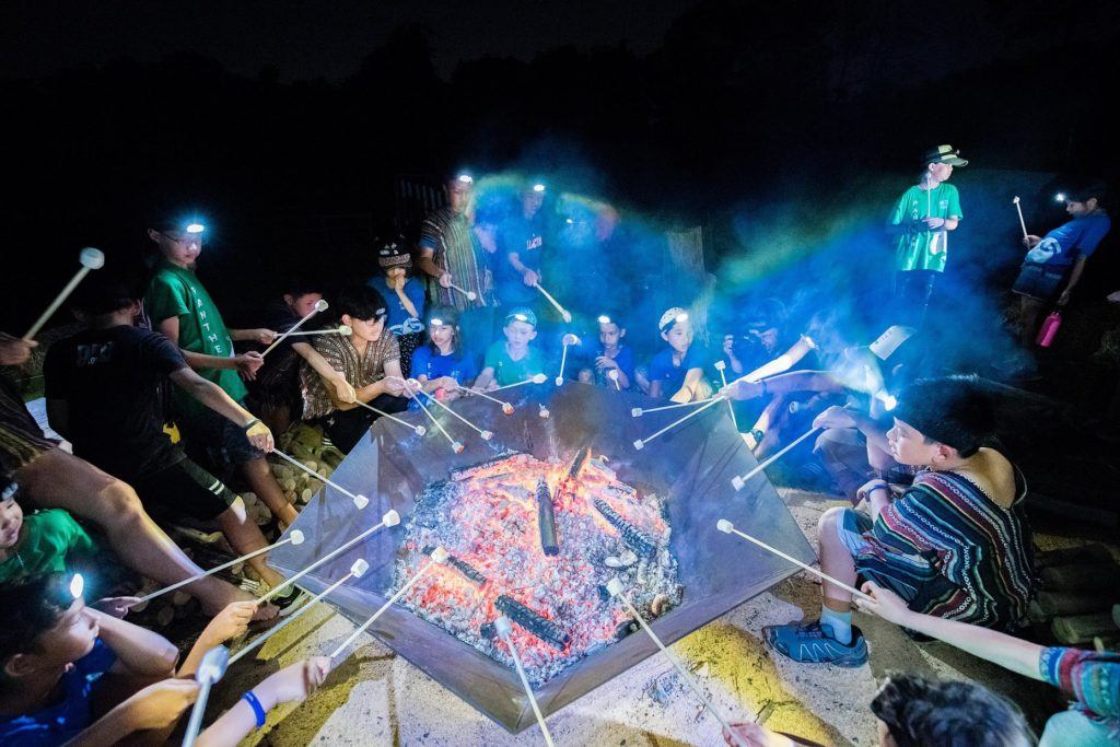 Lots of children toasting marshmallows at a camp fire - Rugby School Thailand