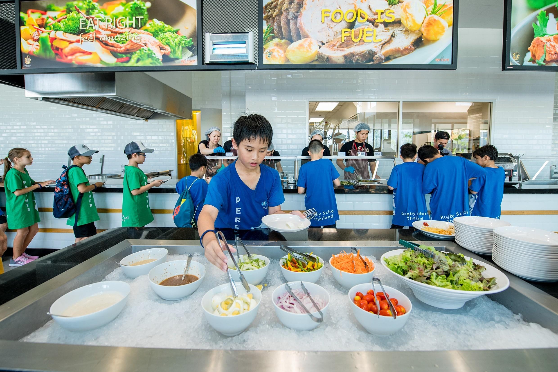 A boy choosing lunch at Rugby School Thailand Holiday Camp