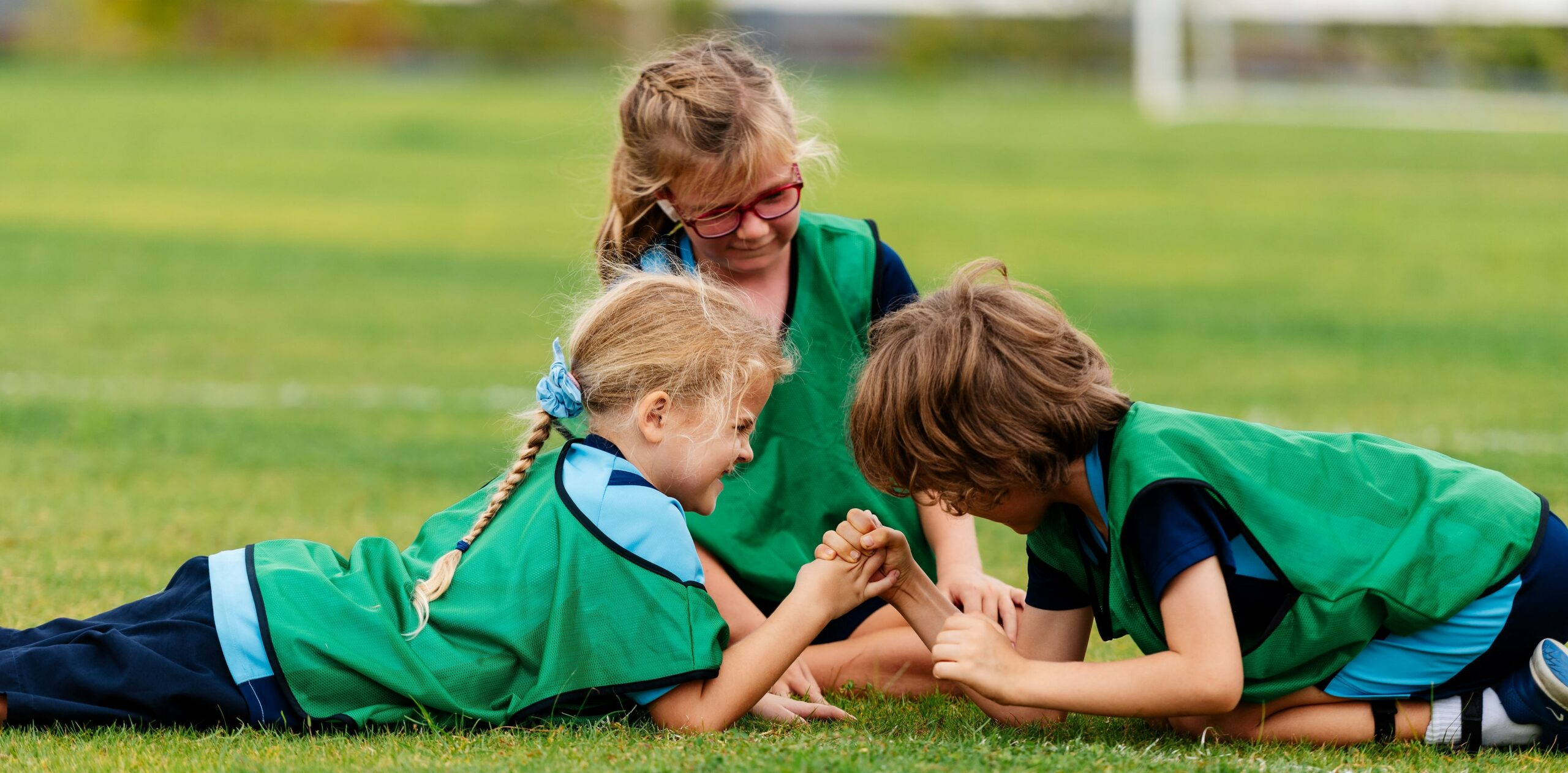 Two children playing an arm wrestle at Rugby School Thailand